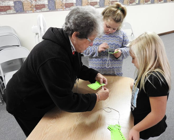 Volunteer Bonnie Hague helps Zoey Mounts and Daisy Hawthorne sew together paper dresses during a recent lesson on Adam and Eve at Lifewise Academy at Conesville United Methodist Church. The release time programs offers religious teachings to students at Conesville Elementary School with parental permission