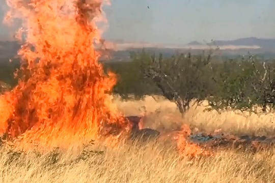 In this frame grab from a April 23, 2017, video provided by the U.S. Forest Service, is a gender reveal event in the Santa Rita Mountain's foothills, more than 40 miles southeast of Tucson, Arizona, as a fire begins to burn. The explosion from the reveal ignited the 47,000-acre Sawmill Fire. Gender reveal parties with a blast of color, pink or blue, that were once considered private gatherings have become social media spectacles, sometimes with dangerous consequences. (U.S. Forest Service via AP)