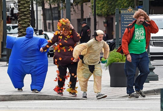 A cold wind threatens to blow away Halloween revelers crossing Canal Street in New Orleans, La. Thursday, Oct. 31, 2019. The U.S. National Weather Service issued a Wind Advisory 10:00 PM on Halloween.