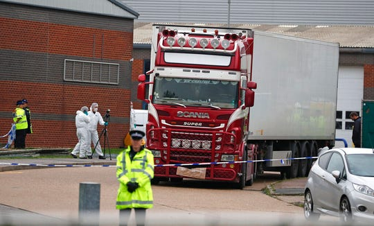 In this Oct. 23, 2019, file photo, police forensic officers attend the scene after a truck was found to contain a large number of dead bodies, in Thurrock, South England.