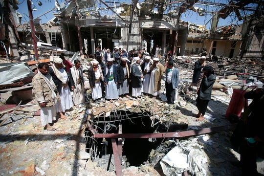 In this Oct. 13, 2016 file photo, members of the Higher Council for Civilian Community Organization inspect a destroyed funeral hall as they protest against a deadly Saudi-led airstrike on a funeral hall in Sanaa, Yemen. A database project that tracks violence says Yemen's civil war has left more than 100,000 people dead since 2015. The Armed Conflict Location & Event Data Project, or ACLED, said Thursday, Oct. 31, 2019, the war's death toll includes more than 12,000 civilians killed in attacks directly targeting civilians.