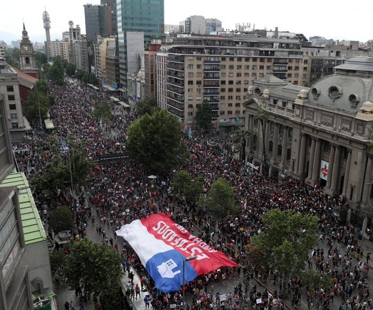Anti-government demonstrators march in Santiago, Chile, Friday, Oct. 25, 2019. A new round of clashes broke out Friday as demonstrators returned to the streets, dissatisfied with economic concessions announced by the government in a bid to curb a week of violence that began with a protest over a hike in subway fares.