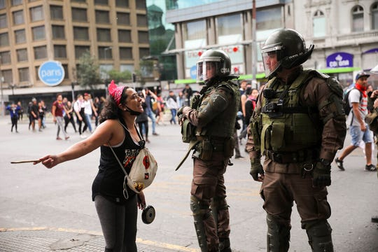 An anti-government demonstrator confronts a couple of police officers in riot gear during a women's march against President Sebastian Pinera in Santiago, Chile, Friday, Nov. 1, 2019.