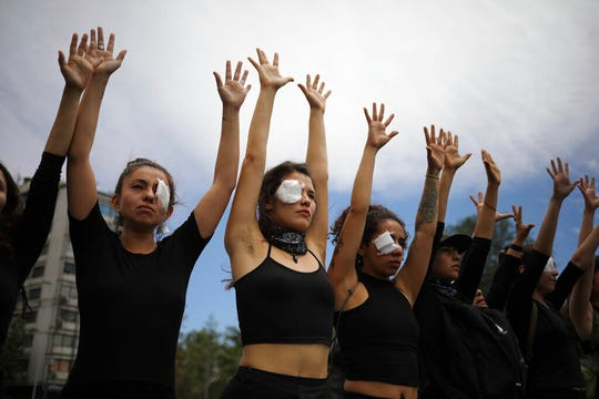 Women dressed in black perform to mourn those who have been killed, tortured and raped during an anti-government protest in Santiago, Chile, Friday, Nov. 1, 2019. Chile has been facing days of unrest, triggered by a relatively minor increase in subway fares. The protests have shaken a nation noted for economic stability over the past decades, which has seen steadily declining poverty despite persistent high rates of inequality.