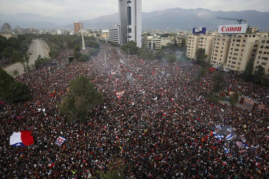 In this Oct. 25, 2019 photo, people gather during an anti-government protest in Santiago, Chile.