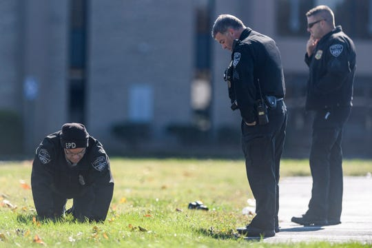 Evansville Police Department officers search for evidence after a shooting took place in a parking lot near Memorial Baptist Church along Walnut Street in Evansville, Friday afternoon, Nov. 1, 2019.
