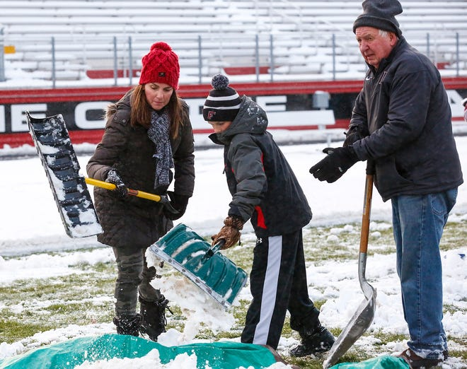 Robin and Brody Haus and Art Godleski were among more than a dozen people who came out  Thursday, October 31, 2019 to help clear several inches of snow off Fruth Athletic Field for Friday's level two playoff game against Sun Prairie. Doug Raflik/USA TODAY NETWORK-Wisconsin