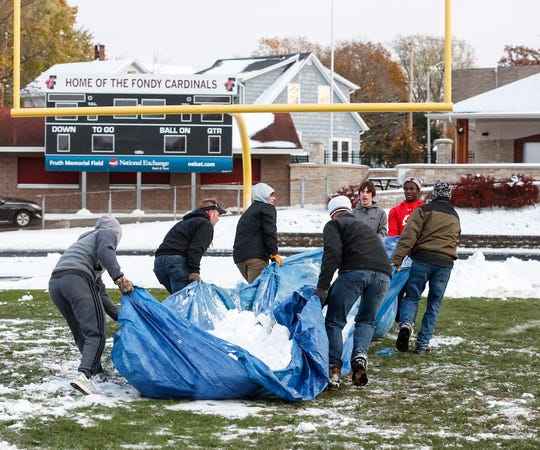 Several Fond du Lac High School football players haul a tarp full of snow Thursday, October 31, 2019 as they and other volunteers clear several inches of snow off Fruth Field in time for Friday's level two playoff game against Sun Prairie. Doug Raflik/USA TODAY NETWORK-Wisconsin
