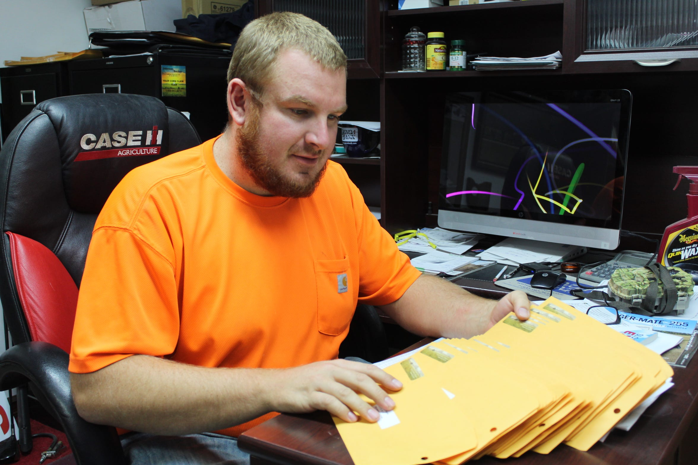 Genoa farmer Chad Gargas shows the pile of envelopes, which include rent checks and his annual newsletters, that he will mail to absentee landlords, insurance agents and farm cooperatives by Nov. 1.