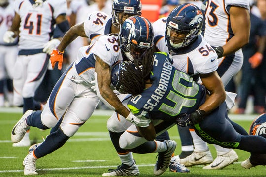 Denver Broncos linebacker Josh Watson, right, and defensive back Trey Marshall tackle Seattle running back Bo Scarbrough during a preseason game Aug. 8, 2019, in Seattle. Watson, an undrafted rookie free agent from Colorado State, was promoted Friday from the Broncos practice squad to the active roster.