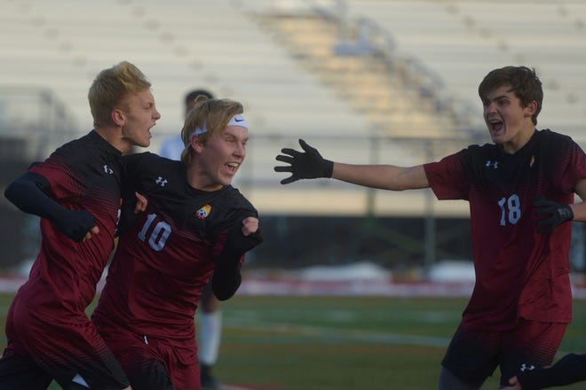 Rocky Mountain soccer players, from left, Riley Eberling, Mike Madden and Payton Petrilli celebrate the game-winning goal scored by Eberling in the Lobos 2-1 overtime victory over Aurora Central in the first round of the 5A playoffs on Friday, Nov. 1, 2019 at French Field.