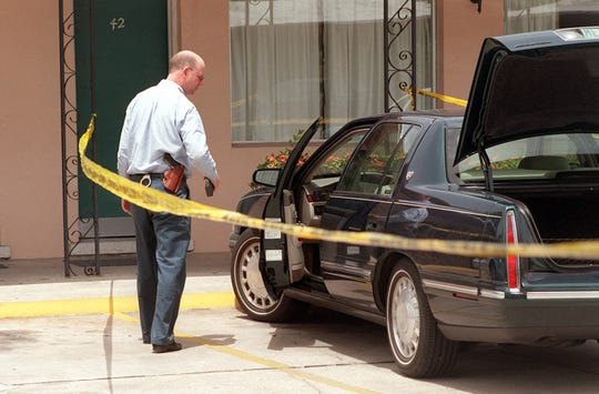 Then Fort Myers police department detective Charlie Lawson looks over the car of Keith Alan Jones who was found shot to death  in room 42 at the Tides Motel, 2621 First St., on June 19, 1997.