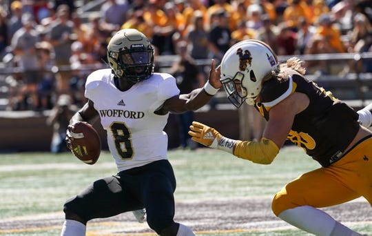 Wofford quarterback Joe Newman (8) stiff arms Wyoming safety Andrew Wingard (28) during their game in 2018.