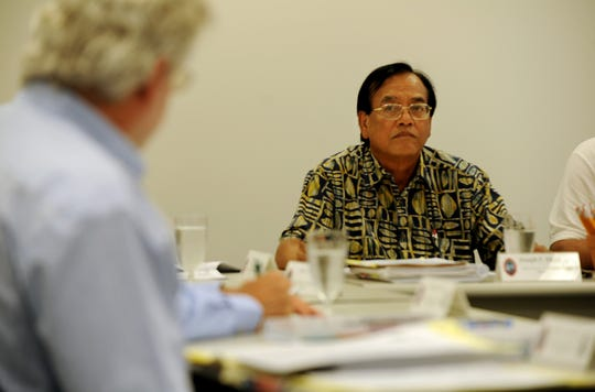 Joseph Mesa listens to attorney Jeff Cook at a Guam Election Commission meeting in this 2012 file photo.