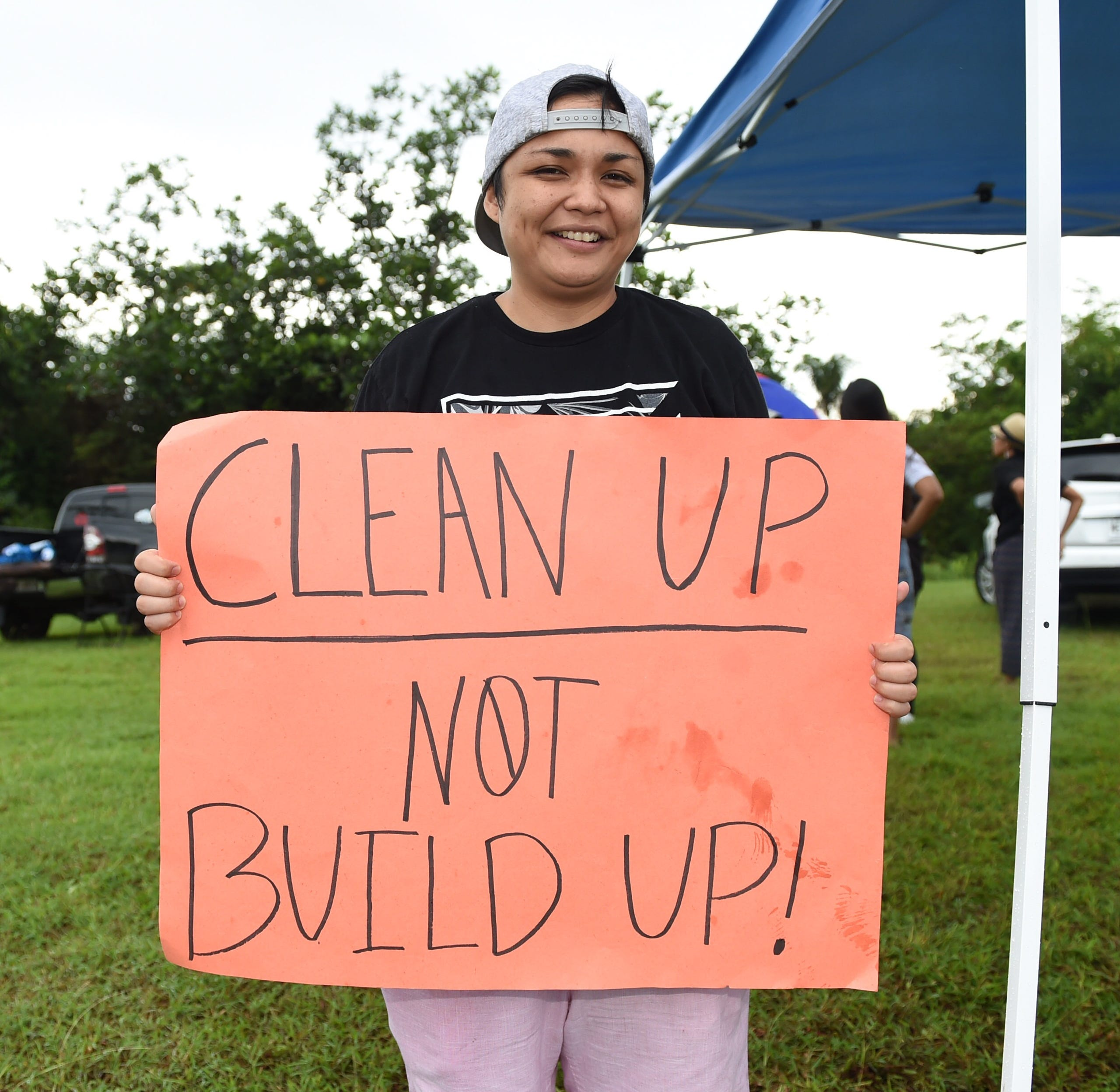 Stacy Salas holds a sign during a peaceful protest against the military buildup across Joint Region Marianas on Nimitz Hill, Nov. 1, 2019.