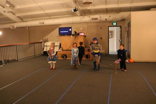 Several children lined up to do horse races in the upstairs annex of Grace Fellowship Church on Halloween night.
