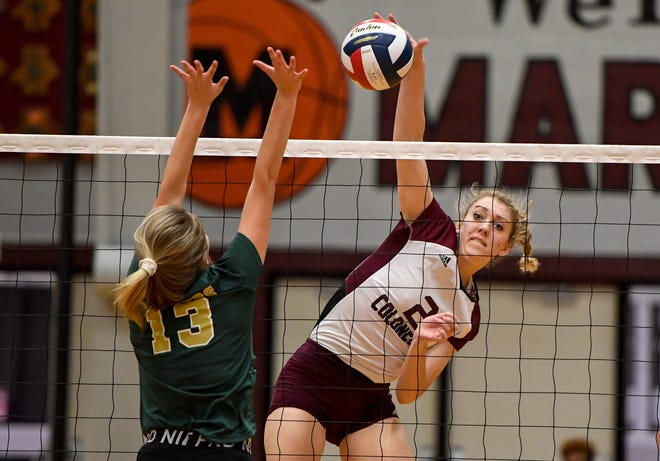 Henderson's Brooke Springer (2) attacks over the new against University Heights' Katie Beth Stevens (13) as the Henderson County Lady Colonels play the University Heights Lady Blazers for the Second Region volleyball tournament championship at Madisonville-North Hopkins High School Thursday evening, October 31, 2019.