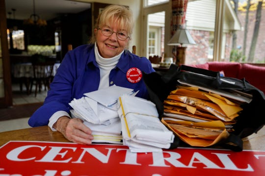 Sue Dillon poses in her home in Carmel, Ind., with some of the petitions gathered to change Indiana time zone.
