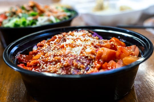 The Reds bowl from Enjoyabowl Fusion Grill is pictured, Friday, Nov., 1, 2019, located at 316 E Burlington Street in Iowa City, Iowa. The bowl consists of braised pork with brown rice, red cabbage, kimchi, tomato, cheese, Korean hots, red curry sauce, and is topped with sesame seeds.