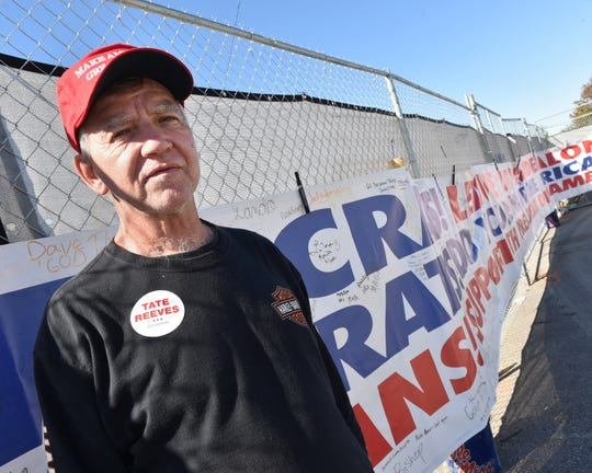 Tony Kane of Yazoo City, Miss. stands outside the BancorpSouth Arena in Tupelo adjacent to a 100 foot sign he created in support President Donald Trump. The sign has been signed by visitors gathering to see Trump and Miss. LT. Gov. Tate Reeves who will speak at the arena tonight on Friday, Nov.1, 2019. The signs message warns both Democrats and Republicans of the danger Kane believes exists in not supporting both Trump and the office of the president.