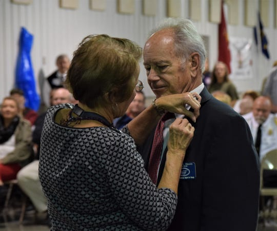 A volunteer with Fairhope Hospice and Palliative Care pins a button to a veteran during the opening ceremony of Freedom's Never Free Oct. 31. The event commemorates military veterans and active members for their service.