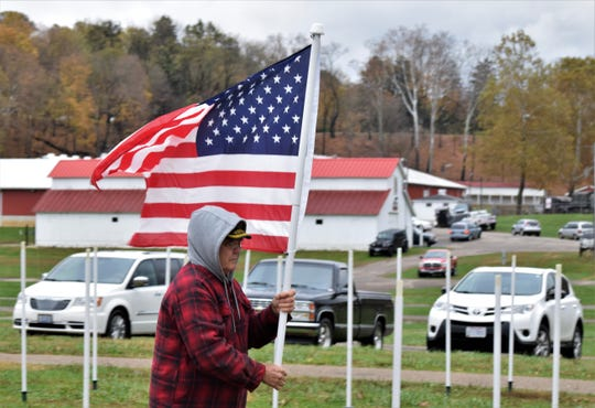 A US Army veteran carries a flag to its post in the Field of Heroes Oct. 31. As part of the Freedom's Never Free event, the flags commemorate military veterans and those members currently serving.