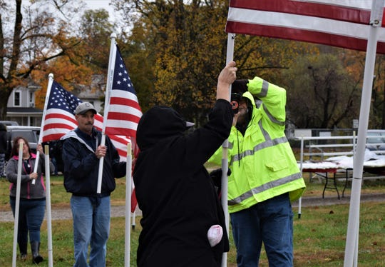 Brenda Phillips posts a flag commemorating her son, who is currently serving in the US Air Force, while her husband George takes a photo, in the Field of Heroes at the Fairfield County Fairgrounds on Oct. 31. It's part of the Freedom's Never Free event, commemorating those who have served and are serving in the the military or as emergency responders.