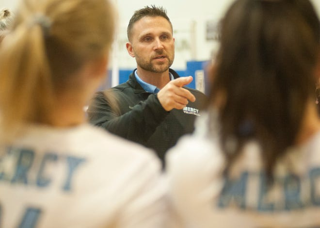 Mercy head volleyball coach Matthew A. Thomerson talks to his players during a time-out of the 6th Regional Volleyball Championship game.31 October 2019