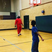 Paul Crosby plays basketball with a child he was mentoring in October 2019.