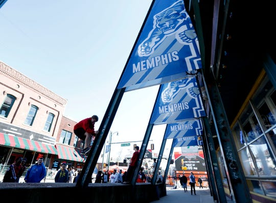 Children climb on the support beams holding University of Memphis banners in front of Silky O'Sullivan's on Nov. 1, 2019, on Beale Street in downtown Memphis.