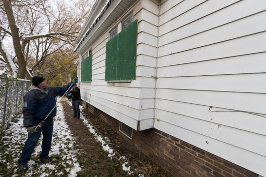 City of Milwaukee Department of Public Workers employee Tom Rowe boards up a house at 1513 N. 37th St. on Friday after city officials cracked down on drug and prostitution activity at the house.