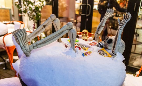 A skeleton display is covered in snow in Cedarburg after a Halloween snowstorm moved across southeastern Wisconsin on Thursday, Oct. 31, 2019.