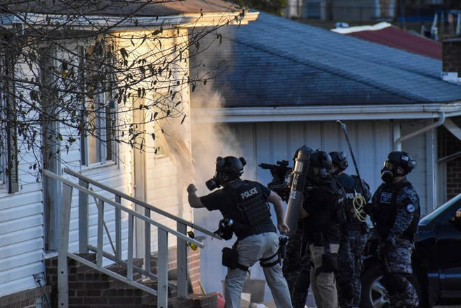 Members of a SWAT team insert gas into a home on Kirkland St. in Gassville during a standoff with manhunt suspect Alton Bruce Cooke.
