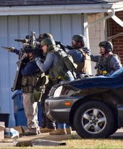 SWAT team members approach a home on Kirkland St. in Gassville during a standoff with manhunt subject Alton Bruce Cooke.