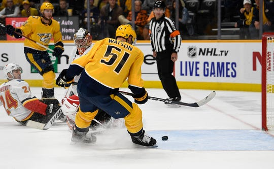 Nashville Predators left wing Austin Watson (51) scores a goal past Calgary Flames goaltender David Rittich (33) and defenseman Travis Hamonic (24) during the third period on Thursday.