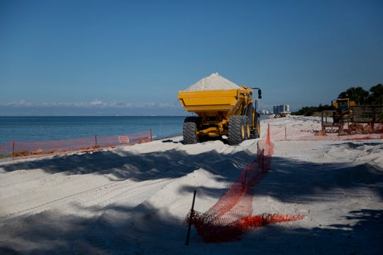 A truck transports sand down the beach as part of Collier County's multi-million dollar beach renourishment project near Park Shore Beach Park in Naples on Friday, November 1, 2019.