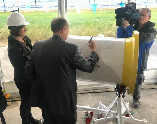 State Sen. Jay Hottinger, R-Newark, signs a water pipe that will be used inside the new Google data center in New Albany.