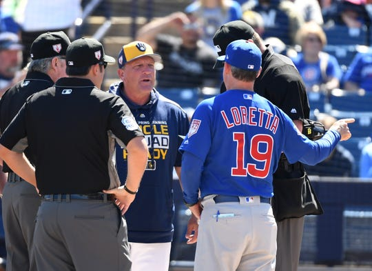 Bench coach Mark Loretta #19 of the Chicago Cubs exchanges lineup cards with bench coach Pat Murphy #59 of the Milwaukee Brewers prior to a spring training game at Maryvale Baseball Park on March 10, 2019 in Phoenix, Arizona.