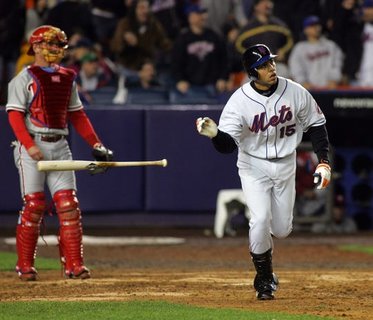 The Mets Carlos Beltran tosses his bat aside after hitting a three-run homer in the 7th inning, as Phillies catcher Mike Lieberthal looks on in Queens on May 2, 2005.