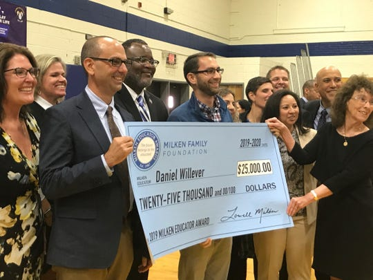 Ramsey School Superintendent Matthew Murphy and State Education Commissioner Lamont Repollet look on as Ramsey social studies teacher Daniel Willever receives $25,000 Milken Family Foundation Award check from Senior Vice President Jane Foley.  It was one of 40 awarded nationwide, but the only one given to a New Jersey teacher.