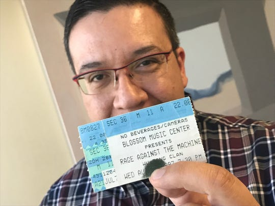 Arts and Entertainment reporter Brian Blueskye holds his ticket stub for a Rage Against the Machine concert in Cuyahoga Falls, Ohio in 1997.