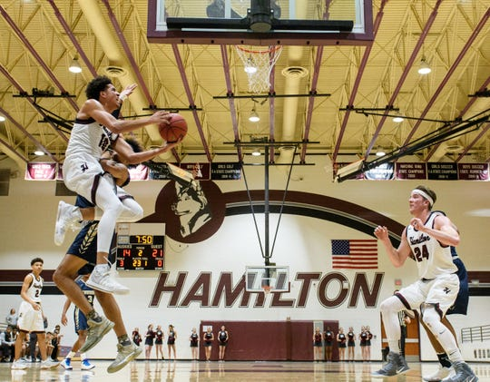 Hamilton's Rashad Smith (10) goes up for a shot with pressure from Desert Vista's Wesley Harris (21) in the second quarter of their game on Friday, Jan. 19, 2018, at Hamilton High School in Chandler, Ariz.