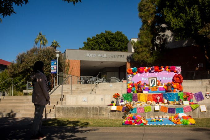 Aide Rodriguez and Trino Sandoval finish an ofrenda on the steps of John Paul Theater at Phoenix College Friday, November 1, 2019.