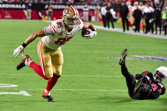 Tight end George Kittle knocks over Cardinals safety Budda Baker en route for a touchdown on Oct. 31 at State Farm Stadium.