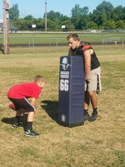 Aiden Pilgrim goes through drills with Almont senior Jacob Hausmann over the summer.