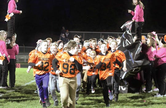 Almont's youth players run onto the field before the varsity football game on Friday, Oct. 25, 2019.