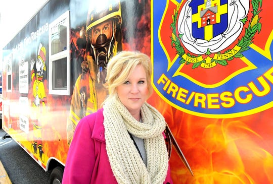 Lisa Altland stands beside the new York City fire safety unit in York City, Friday, Nov. 1, 2019. She and her husband, Greg Altland, a retired York City assistant fire chief, were instrumental in procuring the educational trailer. It was dedicated during First Friday events. Bill Kalina photo