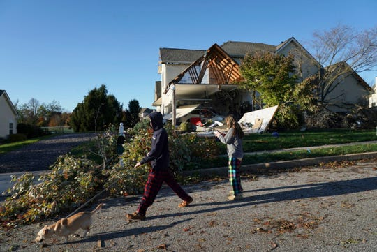 Nearby neighbors Shane wilson, left, and sister Noelle Wilson, center, walk their dog Auggie past a damaged house from Wednesday's storm on in Thornbury Township, Pa, on Friday, Nov. 1, 2019. Homes have been destroyed in Pennsylvania and hundreds of thousands of utility customers were left without power after severe thunderstorms struck the Eastern Seaboard. At least 420,000 customers from South Carolina up to Maine and in Ohio were without power just before midnight Thursday.  (Jessica Griffin/The Philadelphia Inquirer via AP)