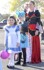 Gwen Egbert (left), 4, sister Alice, 7, and mom Savanah joined in the Alice in Wonderland-themed costumes at the Spooktacular.