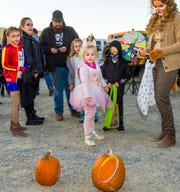 Trunk-or-treaters play a ring toss game.